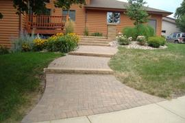 Sloped front entrance walk with VersaLok steps, pillar, and holland pavers.