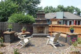Paver patio, built-in bench seats, pillars, and stone fireplace.