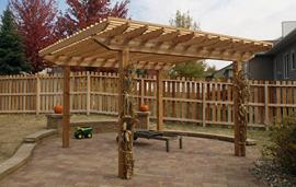Retaining wall around the patio, cedar arbor with two levels on top, VersaLok bench and pillars.