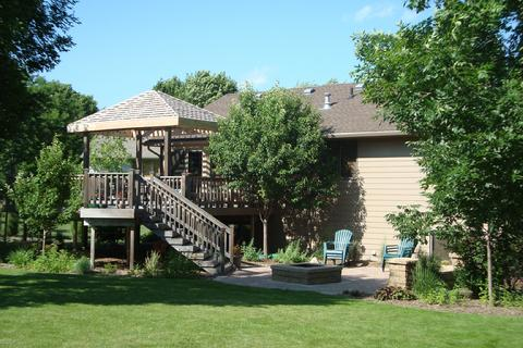Cedar deck with pitched overhead arbor or pergola.  Lower paver patio with buil-in firepit, bench seating and pillars.