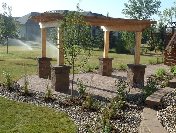 Cedar pergola, overhead, arbor with stone pillars or columns and a paver patio.